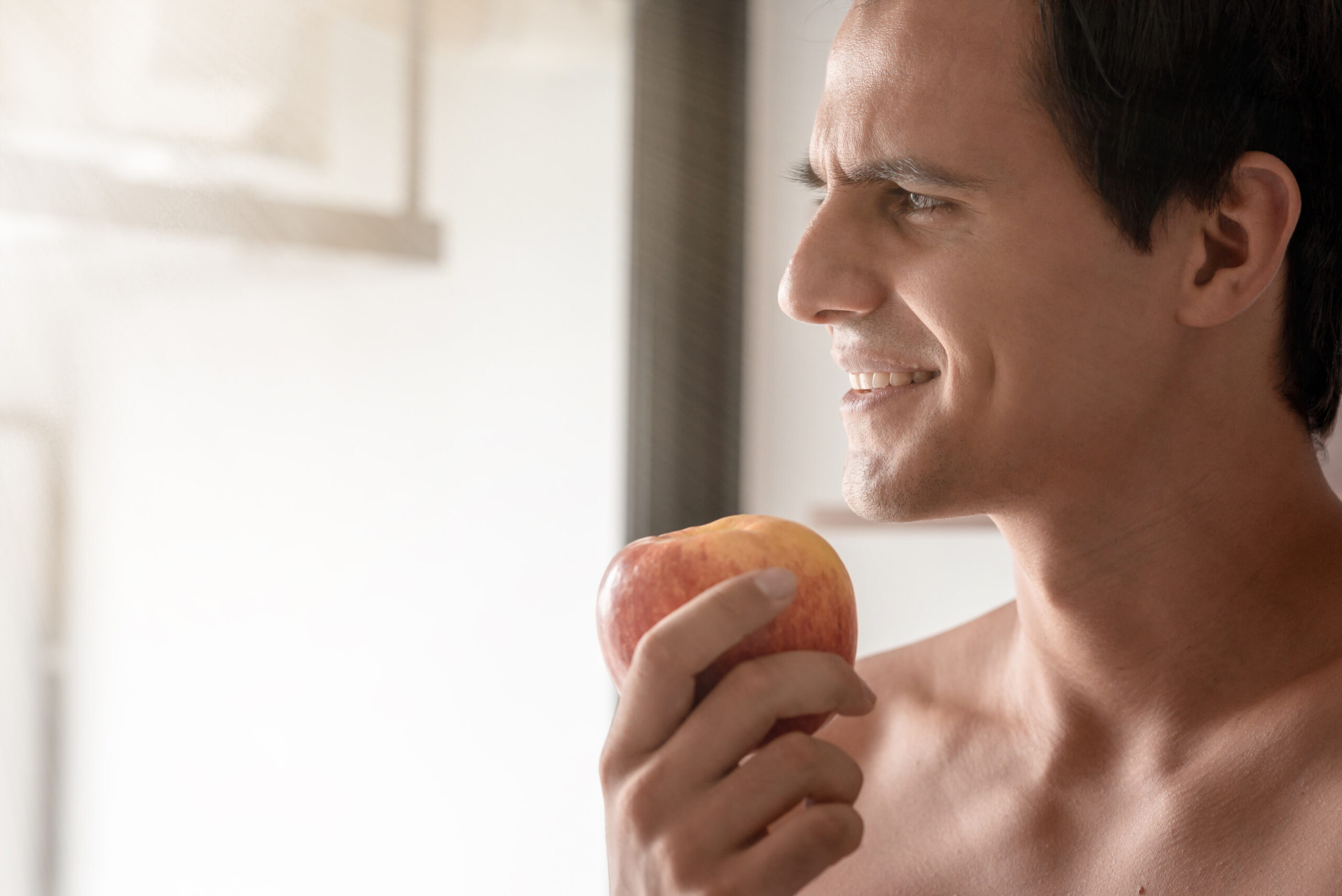 Eat healthy. Man is eating an apple in the morning. Concept of health and diet. Copy space on the left side