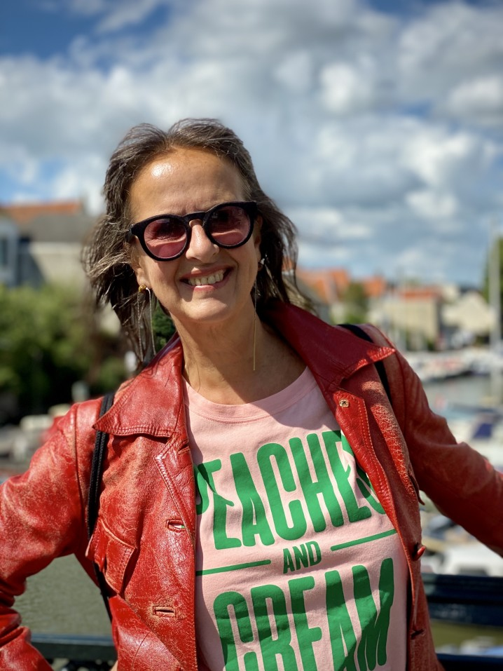 portrait-of-mature-older-attractive-woman-wearing-sunglasses-and-vintage-red-leather-jacket-leaning_t20_aaxRx9